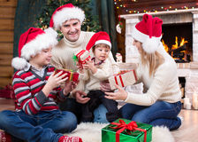 Family exchanging gifts in front of Christmas tree. And fireplace Royalty Free Stock Photos
