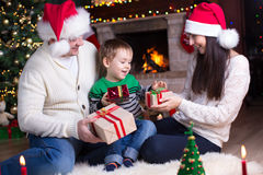Family exchanging gifts in front of fireplace at Christmas tree Stock Photography