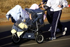 Family Exercising. Family running with their children in strollers Royalty Free Stock Images