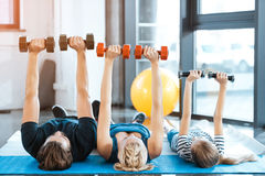 Family exercising with dumbbells at fitness studio