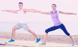 Family exercising yoga poses standing on sunny beach. Young family exercising yoga poses standing on sunny beach by sea in morning Stock Images