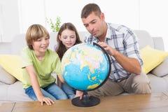 Family exploring globe Stock Photography