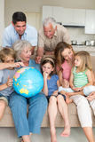 Family exploring globe in living room Stock Photo