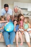 Family exploring globe in living room stock photo