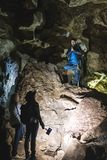 Family exploring huge cave. Adventure travellers dressed cowboy hat and backpack, group of people. vertical photo vacation, stock photos