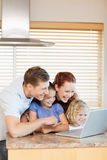 Family exploring the internet in the kitchen Royalty Free Stock Images