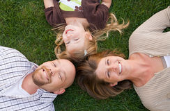 Family Faces. Family Laying Down in the Grass Smiling Royalty Free Stock Image