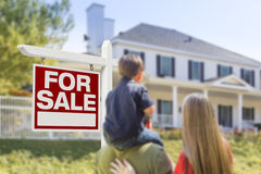 Family Facing For Sale Real Estate Sign and House Stock Photo