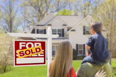 Family Facing Sold For Sale Real Estate Sign and House. Curious Family Facing Sold For Sale Real Estate Sign and Beautiful New House royalty free stock photos