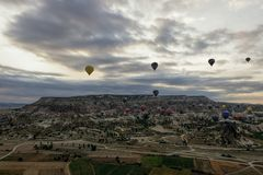 Family of fairy chimneys in Cappadoccia under cloudy early morning skies with hot air balloons in the distance Royalty Free Stock Image