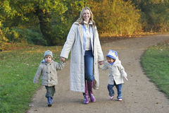 Family In The Fall. A mother, her son and daughter walking through a park filled with autumnal colors Stock Image