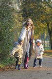 Family In The Fall. A mother, her son and daughter walking through a park filled with autumnal colors Royalty Free Stock Images