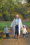 Family In The Fall. A mother, her son and daughter walking through a park filled with autumnal colors Stock Photography