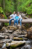Family on a fallen tree across the river Stock Image