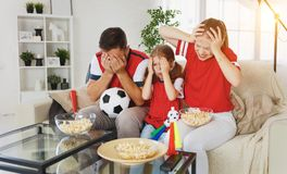 Family of fans watching a football match on TV at home Royalty Free Stock Image