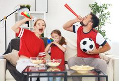 Family of fans watching a football match on TV at home stock photos