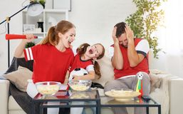 Family of fans watching a football match on TV at home Royalty Free Stock Images