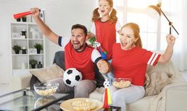 Family of fans watching a football match on TV at home Stock Image