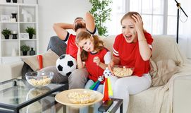 Family of fans watching a football match on TV at home royalty free stock photography