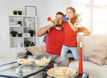Family of fans watching a football match on TV at home stock images