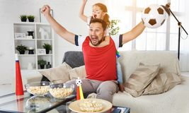 Family of fans watching a football match on TV at home stock photo
