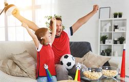 Family of fans watching a football match on TV at home stock photography