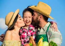 Family farm concept. Parents and daughter farmers celebrate harvest holiday. Family farmers hug kiss kid hold basket. Fall harvest. Family gardener basket stock photo