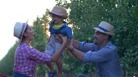 Family of farmers, happy mom and daddy with little child into hats fun spend leisure at garden in sun beam among trees. Family of farmers, happy mom and daddy stock video footage