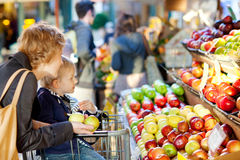 Family at farmers market. Mother and her son buying fruits at a farmers market Royalty Free Stock Photos