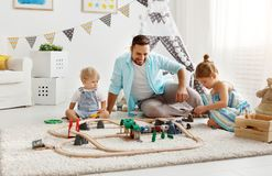 Family father and children play a toy railway in   playroom. Family father and children play a toy railway in the playroom Stock Photography