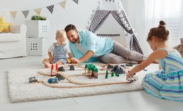 Family father and children play a toy railway in   playroom. Family father and children play a toy railway in the playroom Stock Image