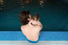Family of father and his little daughter sitting at edge of swimming pool. Young father and his little cute newborn baby Stock Photos