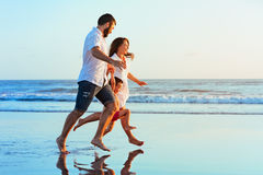 Family - father, mother, baby run on sunset beach. Happy family - father, mother, baby son hold hands, run together with splashes by water pool along sunset sea Royalty Free Stock Image