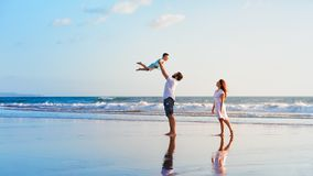 Family - father, mother, baby walk on sunset beach. Happy family holidays. Joyful father, mother, baby son walk with fun along edge of sunset sea surf on black royalty free stock photography