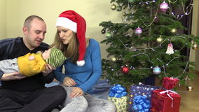 Family father and mother kiss newborn baby daughter in Christmas stock video