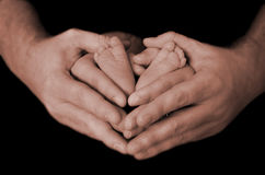 Hands and feet. Father mother and son holding hands and baby feet Stock Photos