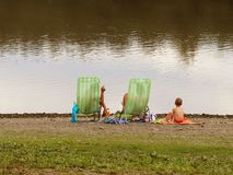 Family: father, mother and son are resting on beach chairs on the shore by the pond. Family holiday on the water. Beach of sand an stock photo