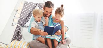 Family father reading to children book in tent at home Stock Images