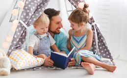 Family father reading to children book in tent at home. Family father reading to children book in tent in playroom at home Stock Image