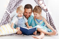Family father reading to children book in tent at home. Family father reading to children book in tent in playroom at home Royalty Free Stock Images