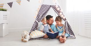 Family father reading to children book in tent at home Royalty Free Stock Photography