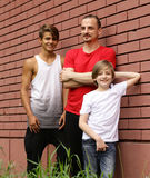 Family, father and sons having fun and posing brick background Royalty Free Stock Images