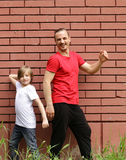 Family, father and sons having fun and posing brick background Royalty Free Stock Image
