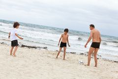 Family father two kids playing football on beach Stock Photo