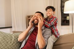 Happy father and little son playing at home. Family, fatherhood, leisure and people concept - happy smiling father and little son playing at home stock photo