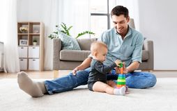 Father playing with little baby daughter at home. Family, fatherhood and people concept - happy father and little baby daughter playing with pyramid toy at home stock photo