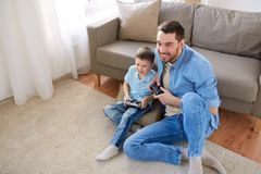 Father and son playing video game at home. Family, fatherhood and people concept - happy father and little son with gamepads playing video game at home Stock Images