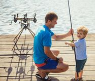 Family, fathers day, childhood. Fishing, angling, activity, adventure. Vacation, hobby, lifestyle. Man and child boy fishing with rods on wooden pier. Father stock photos