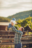 Family feeding horses in a meadow Stock Image