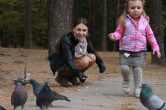 Family feeding pigeons together Stock Photo
